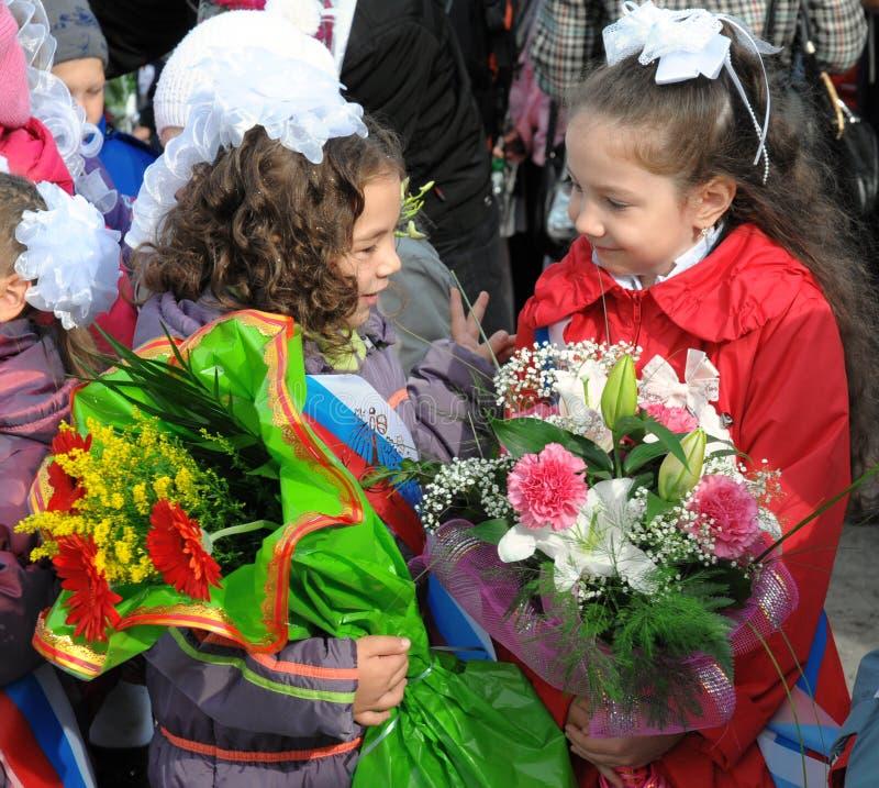 Primeiro-graduadores com as flores na festa do primeiro setembro foto de stock