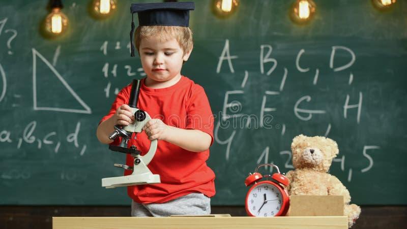 Primeiro interessado anterior no estudo, aprendendo, educação Criança na cara ocupada perto do microscópio Conceito esperto da cr fotografia de stock royalty free