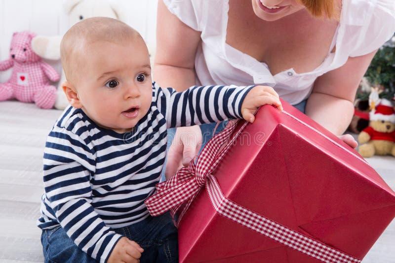 Primeiro Natal: bebê que agita a caixa de presente vermelha grande - rapaz pequeno bonito imagem de stock