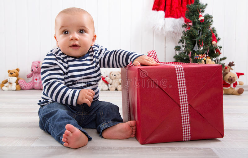 Primeiro Natal: bebê que desempacota um presente vermelho com um checke vermelho fotos de stock royalty free