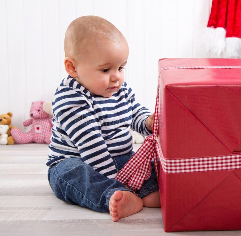 Primeiro Natal: bebê que desempacota um presente vermelho com um checke vermelho imagens de stock