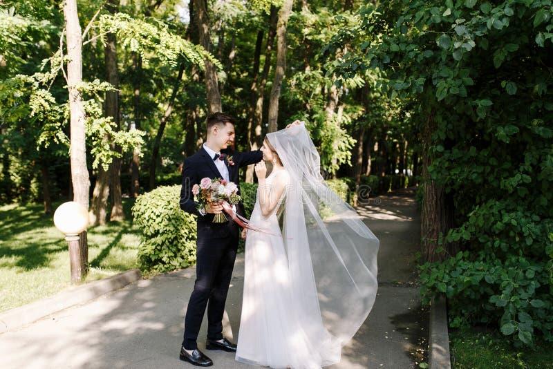 Primeiro olhar, reunião do noivo feliz do sorriso no terno clássico com laço com o ramalhete surpreendente das flores e noiva den fotografia de stock royalty free