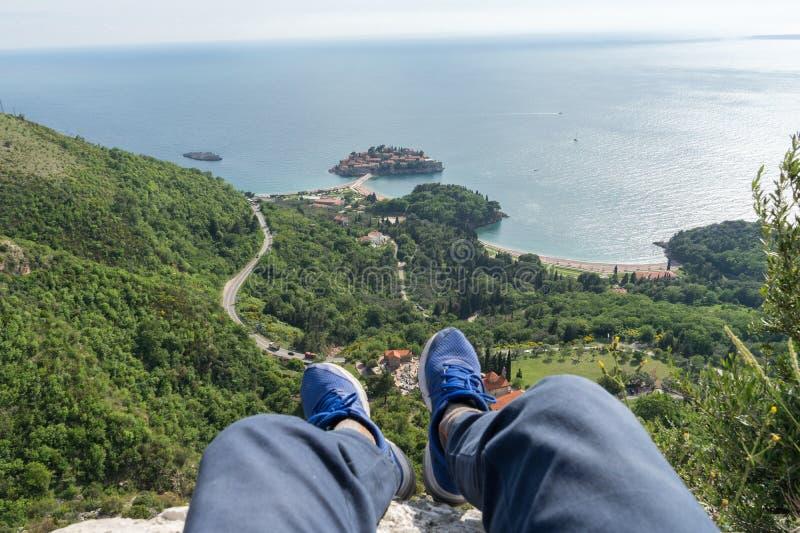 Primeiro sightseeing da perspectiva da pessoa do sveti Stefan em Budva, Montenegro Pés com sapatilhas azuis de um viajante em um  imagens de stock