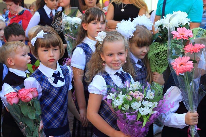 Primeiros graduadores das meninas em uma régua solene o 1º de setembro imagem de stock