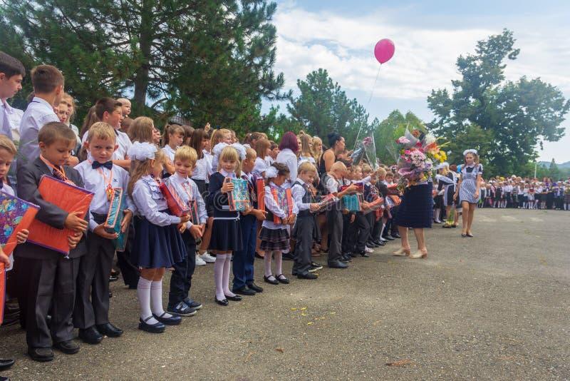 Primeiros graduadores felizes com os presentes em suas mãos no recreio na grande inauguração do ano escolar imagens de stock royalty free