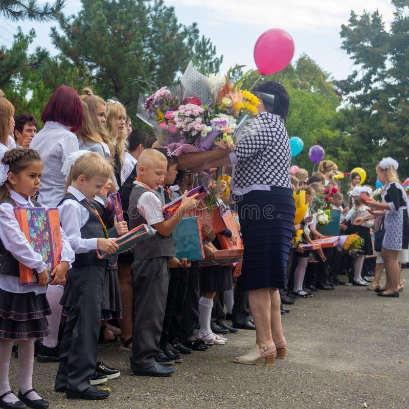 Primeiros graduadores felizes com presentes em suas mãos e em um professor com um ramalhete das flores na jarda de escola na ceri imagens de stock
