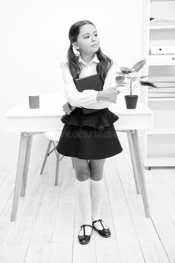 Primer anterior excelente Libro del control del niño de la muchacha mientras que interior blanco de la tabla del soporte Libro fe foto de archivo libre de regalías