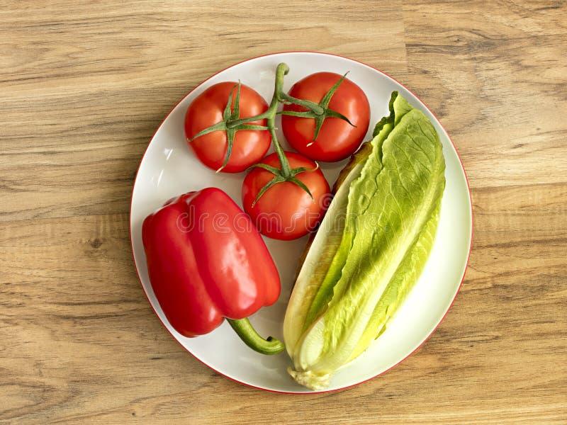 Primer búlgaro de la mentira de la pimienta, del tomate y de la lechuga romana en una placa redonda blanca de la porcelana contra imagen de archivo