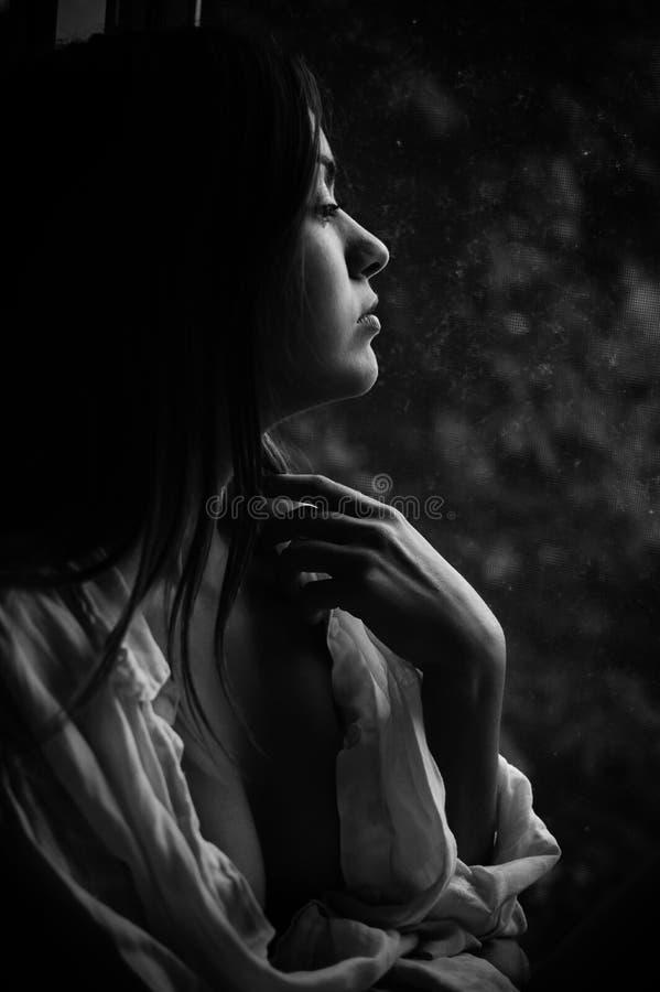 Primer blanco y negro de la fotografía de la mujer bonita joven en la ventana que mira afuera foto de archivo libre de regalías