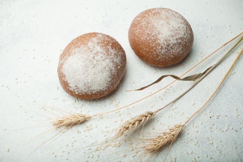 Primer caliente fresco del pan de Rye Bollos negros en harina en un fondo blanco con los puntos del trigo Panadería hecha en casa fotos de archivo