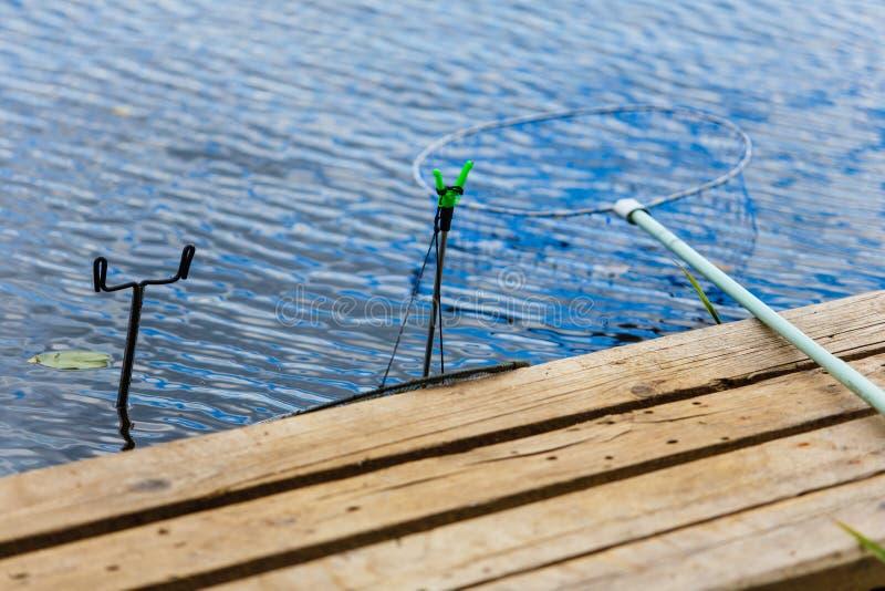 Primer cercano determinado de la orilla del lago del equipo de pesca foto de archivo