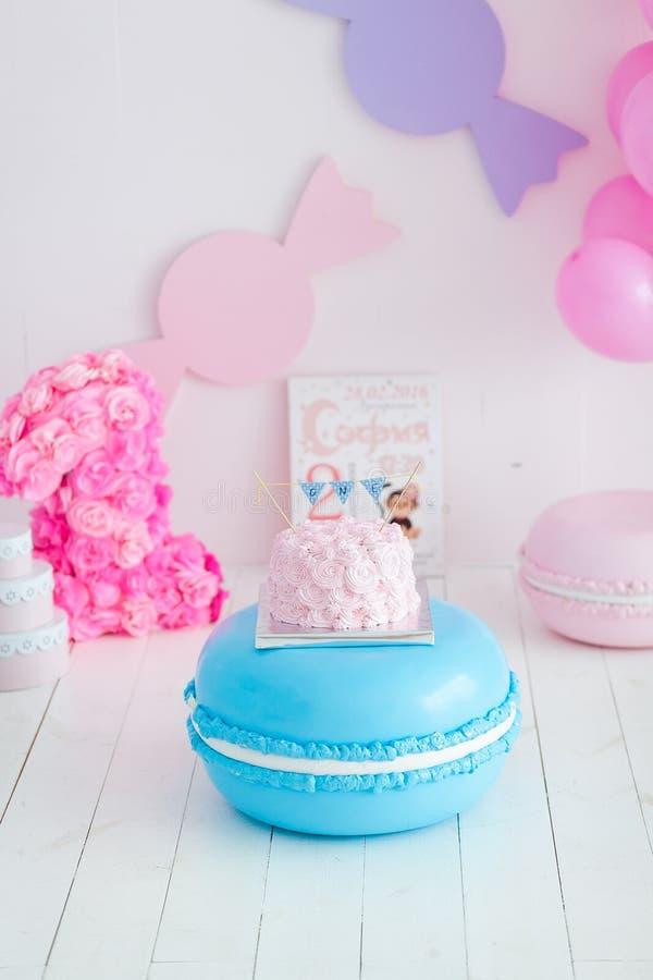 Primer choque del cumpleaños la torta Una torta rosada se coloca en macarrones azules grandes Primer cumpleaños fotos de archivo libres de regalías