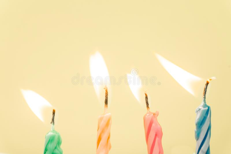 Primer colorido de las velas del feliz cumpleaños con un fondo en colores pastel imagen de archivo