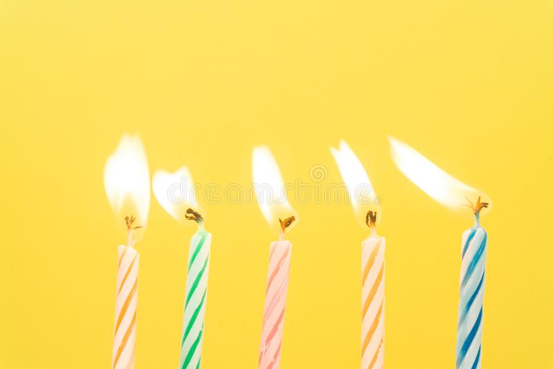 Primer colorido de las velas del feliz cumpleaños con un fondo en colores pastel imagen de archivo libre de regalías