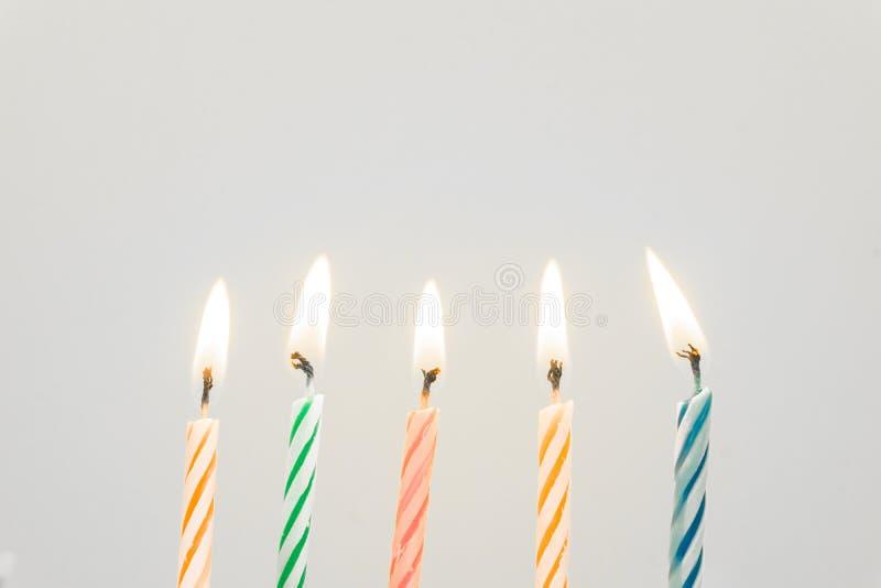 Primer colorido de las velas del feliz cumpleaños con un fondo en colores pastel imagenes de archivo