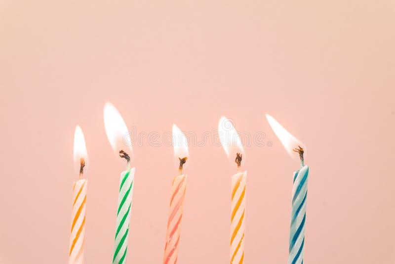 Primer colorido de las velas del feliz cumpleaños con un fondo en colores pastel fotos de archivo