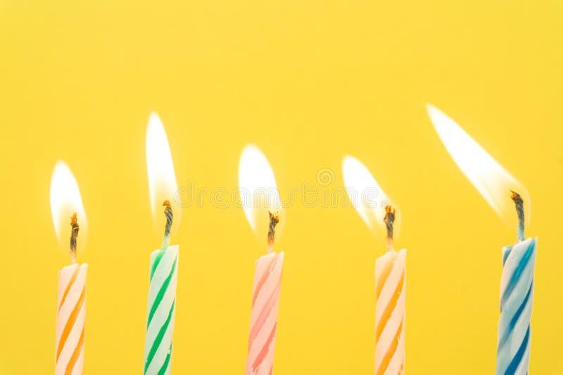 Primer colorido de las velas del feliz cumpleaños con un fondo en colores pastel foto de archivo