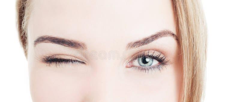 Primer con los ojos hermosos y guiño de la mujer imagenes de archivo