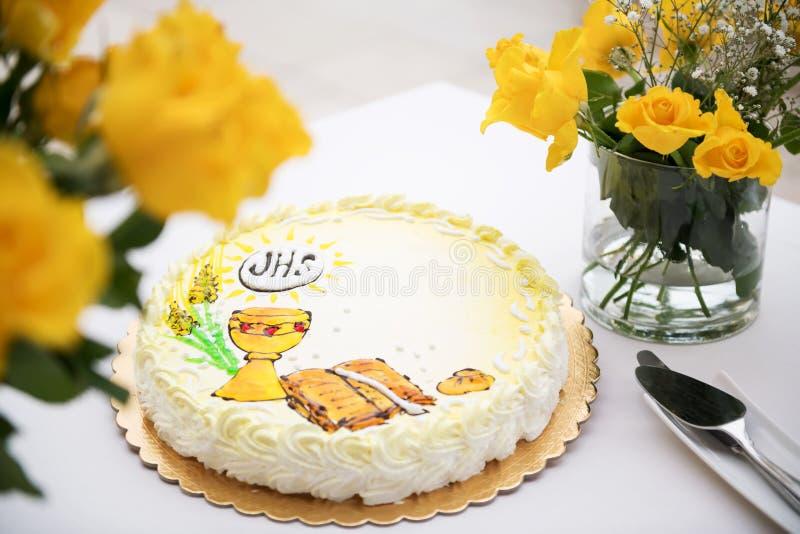Primer concepto de la comunión santa, torta hermosa con la primera comunión santa y rosas amarillas en una tabla blanca foto de archivo libre de regalías