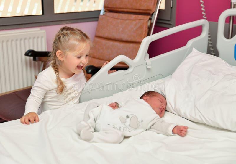Primer conocido entre una hermana y un bebé recién nacido en la sala de hospital imagenes de archivo