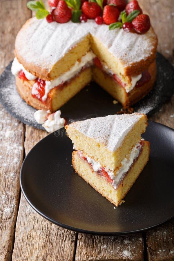 Primer cortado de la torta de esponja de Victoria en una placa vertical imagen de archivo