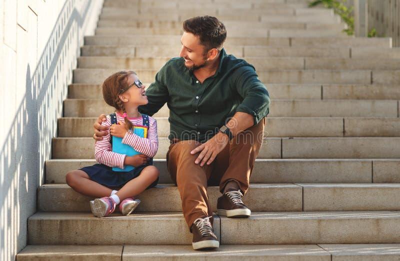 Primer día en la escuela el padre lleva a la colegiala del pequeño niño en f fotos de archivo libres de regalías