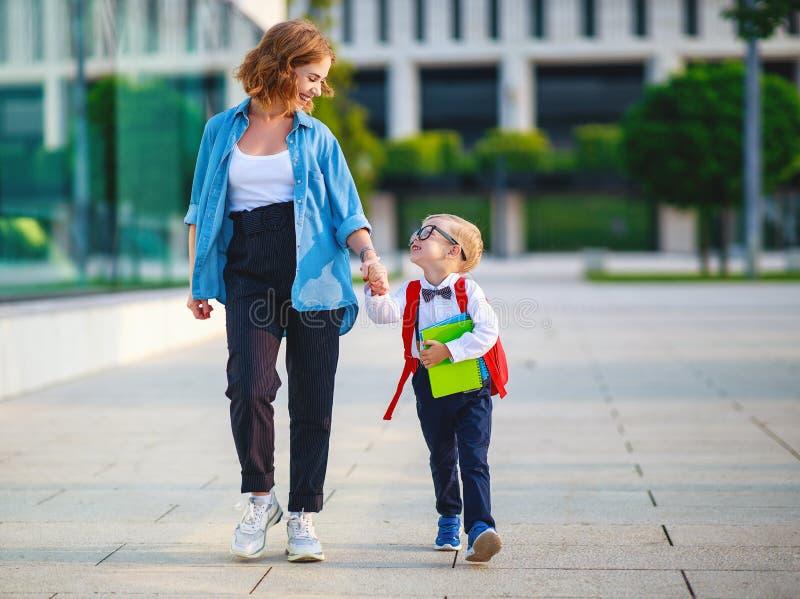 Primer d?a en la escuela la madre lleva al escolar del pequeño niño en el primer grado imagenes de archivo
