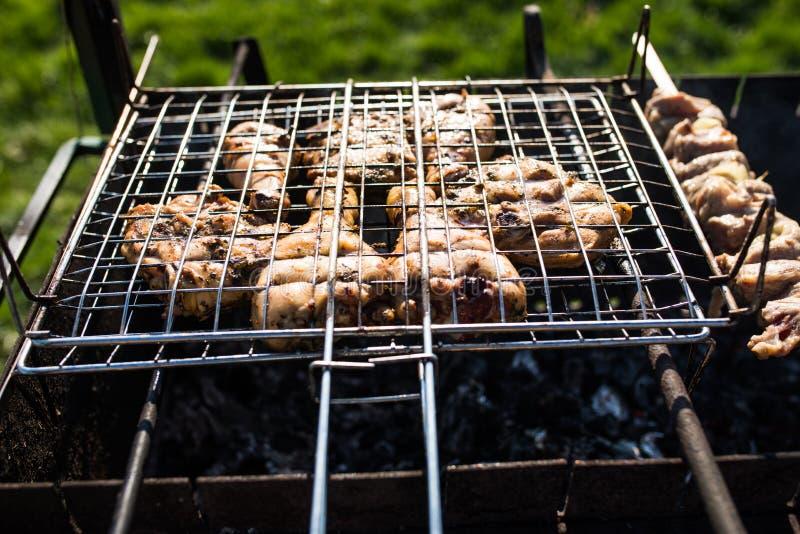 Primer de algunos pinchos de la carne que son asados a la parrilla en una barbacoa Asado a la parilla del shashlik adobado en una fotos de archivo libres de regalías