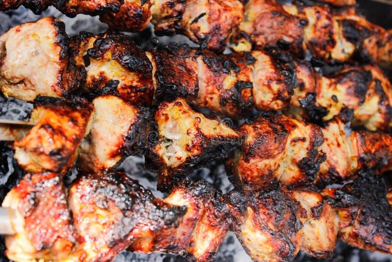 Primer de algunos pinchos de la carne que son asados a la parrilla en una barbacoa fotografía de archivo libre de regalías