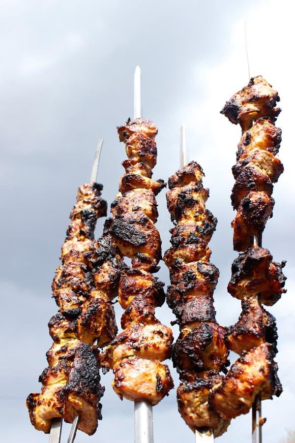 Primer de algunos pinchos de la carne que son asados a la parrilla en una barbacoa imagen de archivo libre de regalías