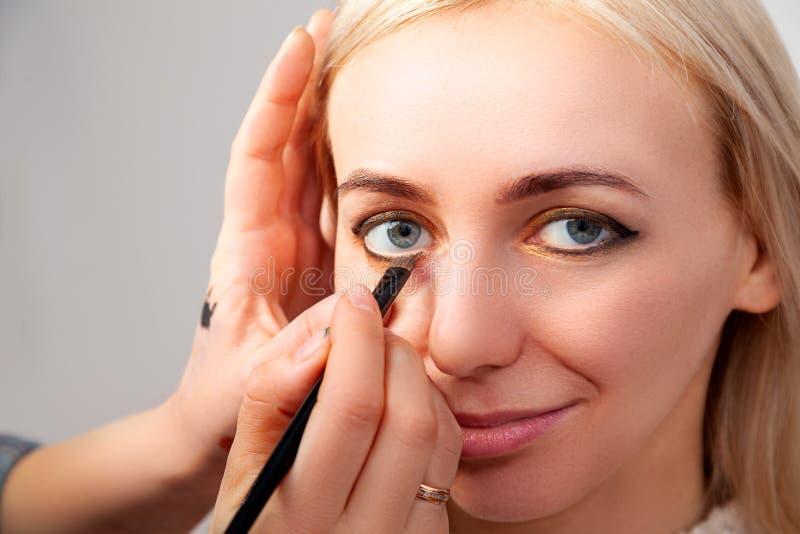 Primer de aplicar maquillaje en el salón en el modelo con los ojos abiertos en el estilo oriental, el artista que pone marrón de  imágenes de archivo libres de regalías