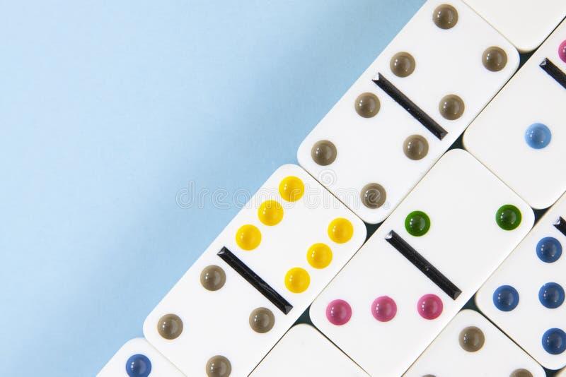 Primer de arriba de los dominós blancos con los puntos brillantemente coloreados en un fondo azul con el espacio de la copia imágenes de archivo libres de regalías
