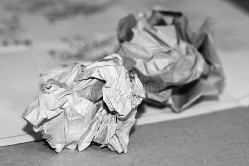 Primer de bolas de papel arrugadas en un fondo de madera blanco con los lápices y las virutas del lápiz imagen de archivo