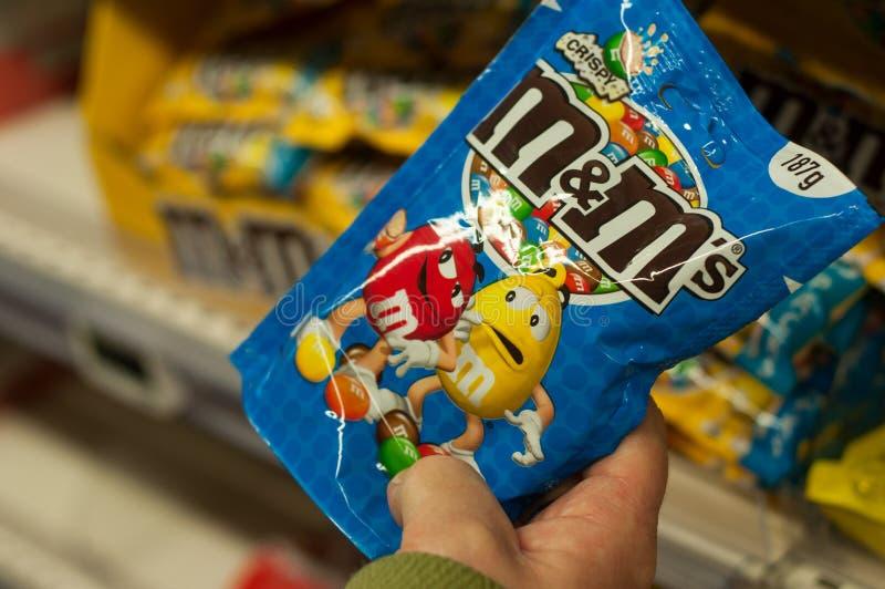 Primer de cacahuetes recubiertos de chocolate de la marca de M y del ` s de m a disposición en el supermercado estupendo de U imagen de archivo