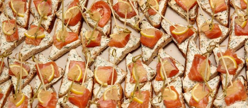 Primer de canapes con el queso cremoso, los salmones, los verdes y el limón foto de archivo