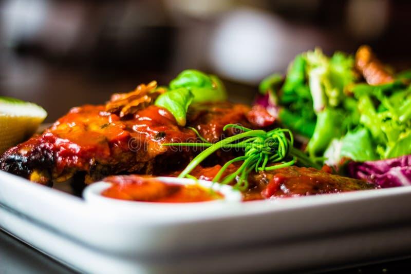 Primer de chuletas de cerdo con la ensalada, la salsa de chile y el baguette en el res fotos de archivo
