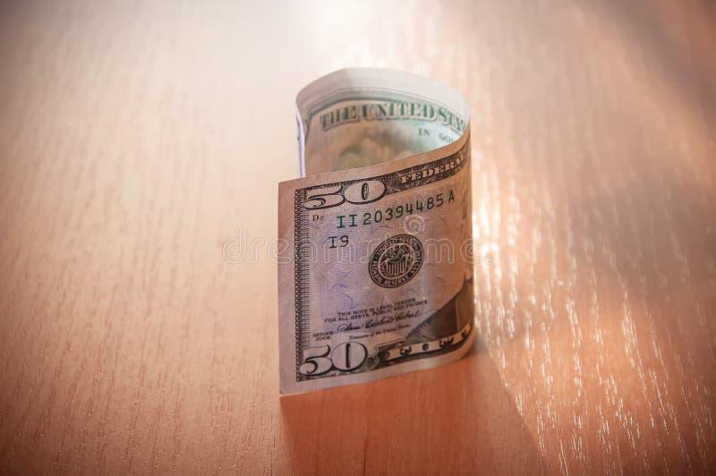 Primer de cincuenta billetes de dólar en la tabla de madera imagen de archivo