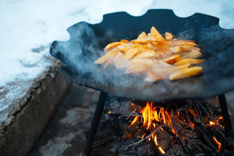 Primer de cocinar las patatas en una cacerola plana en la hoguera al aire libre de invierno fotografía de archivo libre de regalías