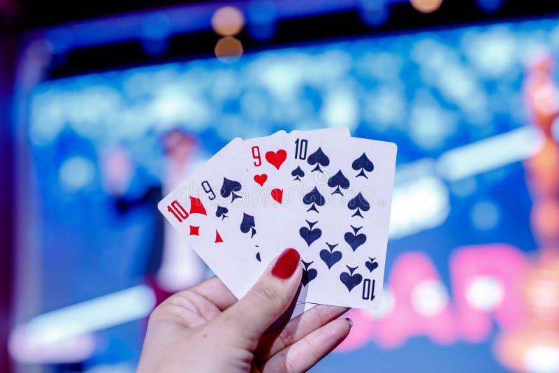 Primer de cuatro naipes mostrados por la mano de la mujer con el fondo borroso Símbolo del ganador Juego de tarjeta del póker fotos de archivo