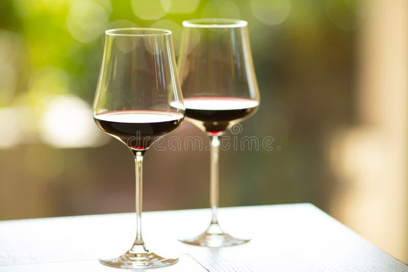 Primer de dos copas de vino rojas con una atmósfera colorida, soleada imagenes de archivo