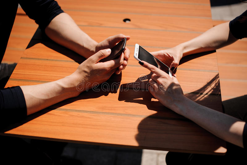 Primer de dos manos de las personas con los teléfonos móviles imagen de archivo