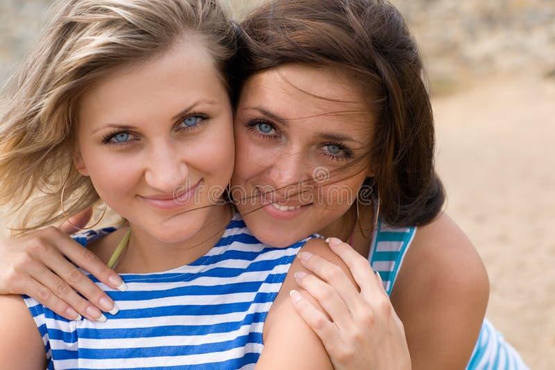 Primer de dos mujeres jovenes que sonríen en la playa foto de archivo