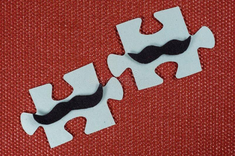 Primer de dos porciones del rompecabezas Hombres simbólicos con un bigote El concepto de compatibilidad psicológica, amistad imagen de archivo