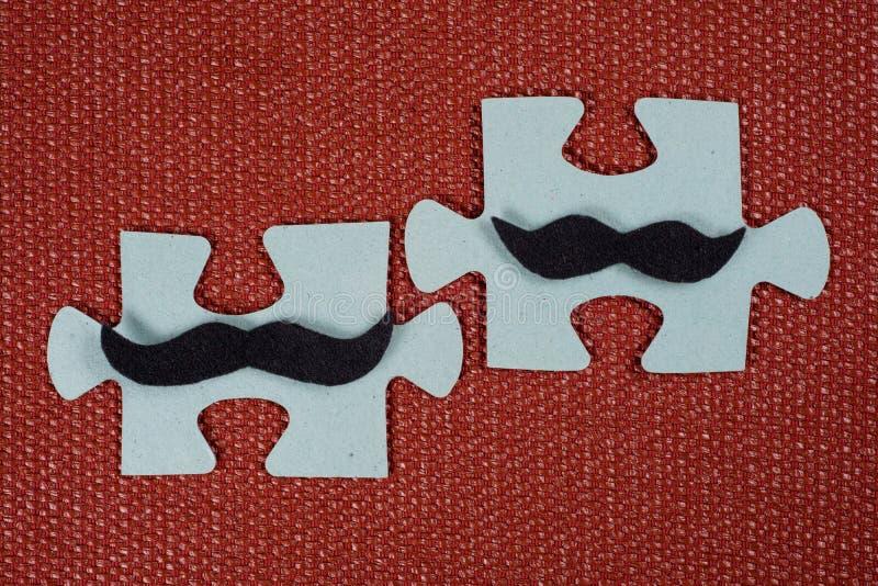 Primer de dos porciones del rompecabezas Hombres simbólicos con un bigote El concepto de compatibilidad psicológica, amistad foto de archivo