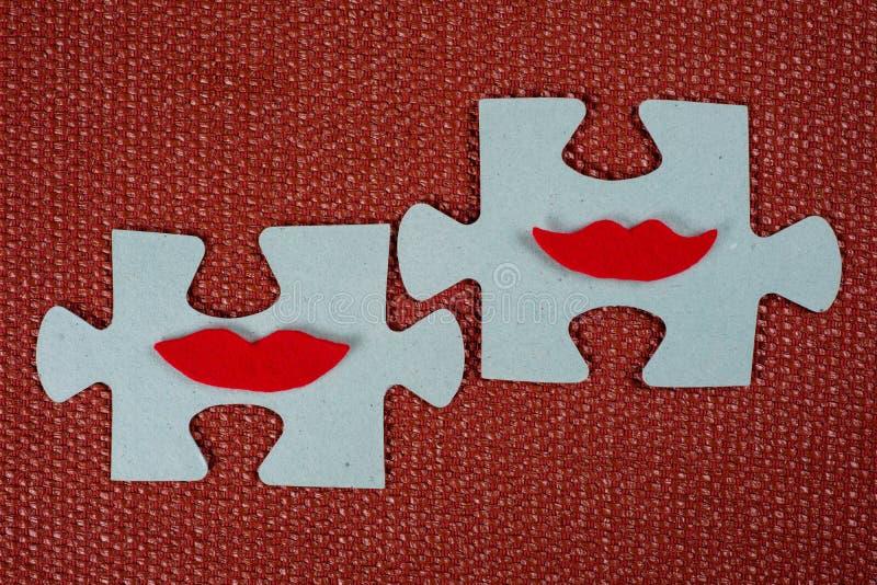 Primer de dos porciones del rompecabezas Mujeres simbólicas con los labios El concepto de compatibilidad psicológica, amistad fotos de archivo