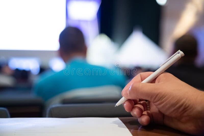 Primer de escribir la mano que toma el examen en el curso imagenes de archivo