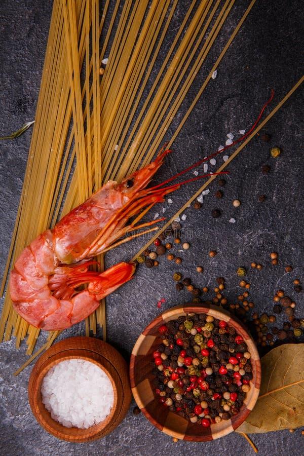 Primer de especias, de espaguetis, del camarón, y de la sal en un fondo concreto negro imagen de archivo libre de regalías