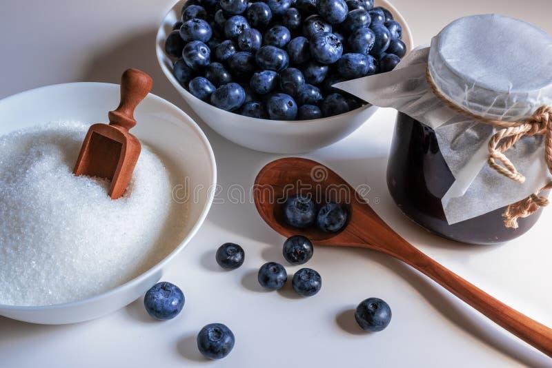 Primer de Huckleberry Jam Arándano y azúcar y cuchara de madera en un cuenco en la cocina imagenes de archivo