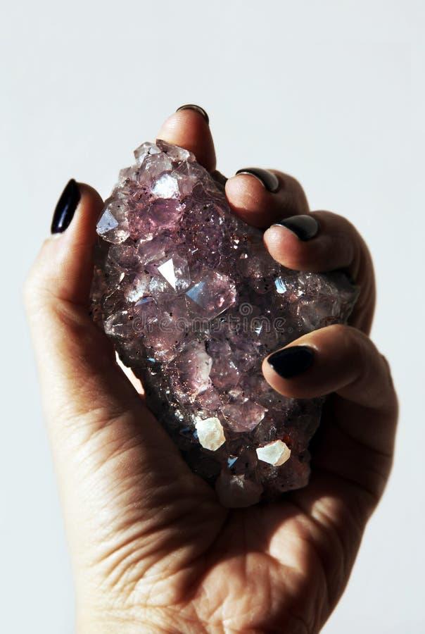 Primer de la amatista de la piedra preciosa de la tenencia de la mano con los cristales de cuarzo de la roca fotografía de archivo libre de regalías