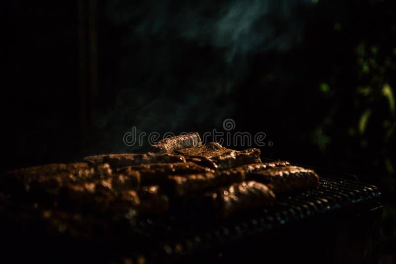 Primer de la barbacoa con la carne en la noche fotografía de archivo
